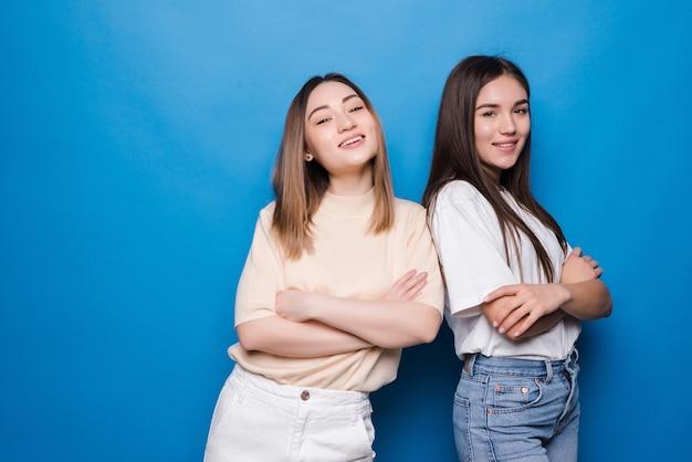Dos mujeres insatisfechas posando aislado en la pared azul amarillo. concepto de estilo de vida de personas. burlarse del espacio de la copia. tomados de la mano cruzados