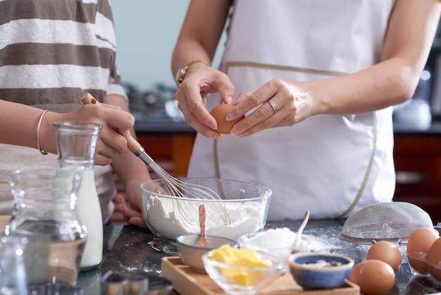 Dos mujeres irreconocibles que sostienen el batidor y rompen el huevo en un tazón