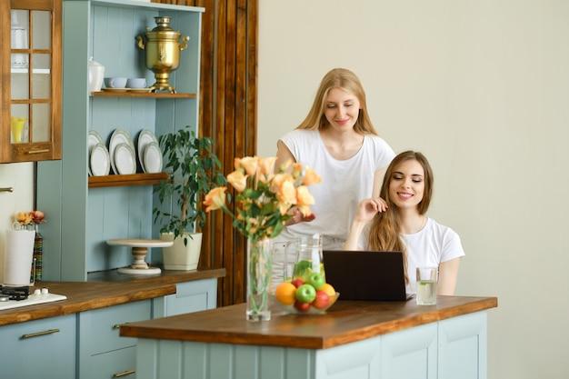 Dos mujeres jóvenes alegres haciendo videollamadas en línea en una computadora portátil, renunciando a las manos y riendo