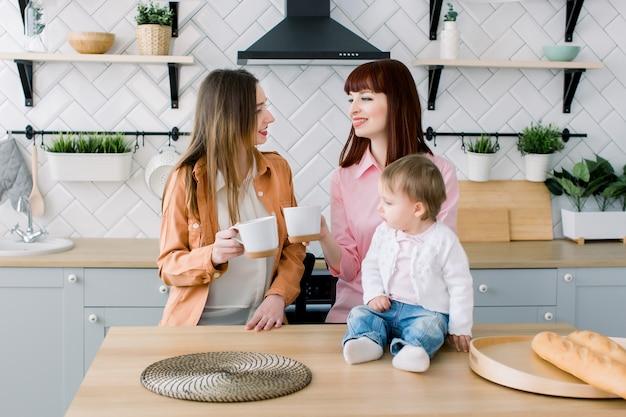 Dos mujeres jovenes alegres que se sientan en una tabla con las tazas en una cocina. la pequeña niña está sentada sobre la mesa. desayuno, concepto de amistad