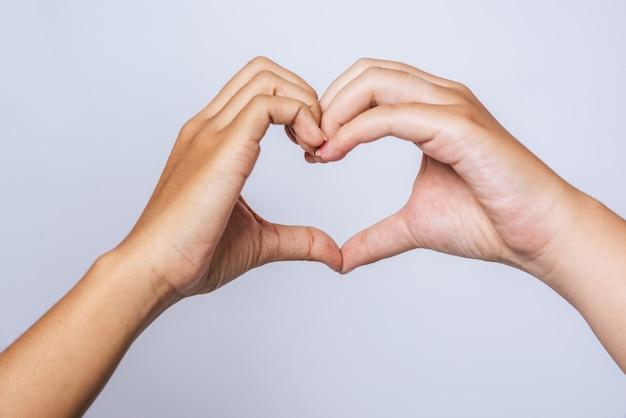 Dos mujeres jóvenes se aman en forma de corazón de marca de mano. Foto gratis