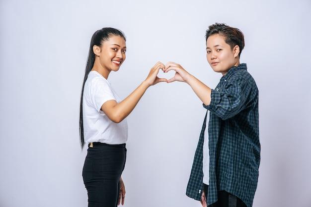 Dos mujeres jóvenes se aman en forma de corazón de marca de mano.