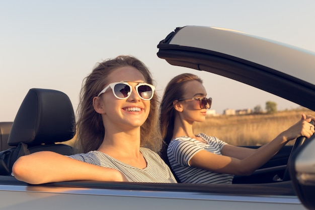 Dos mujeres jóvenes atractivas en un auto descapotable