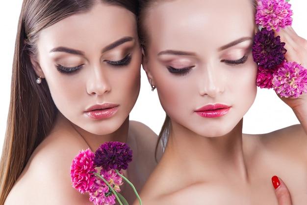 Dos mujeres jóvenes atractivas retrato de belleza de hermosas damas. cosméticos, pestañas de cerca. retrato de moda