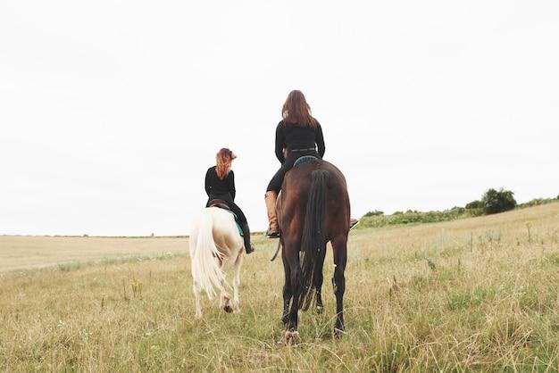 Dos mujeres jóvenes a caballo en un campo. les encantan los animales y la equitación.