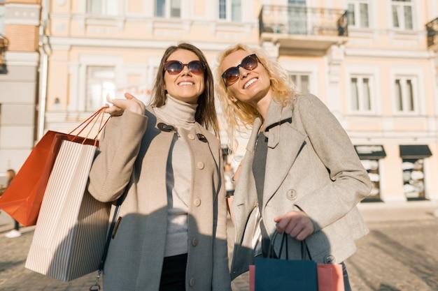 Dos mujeres jóvenes en una calle de la ciudad con bolsas de compras