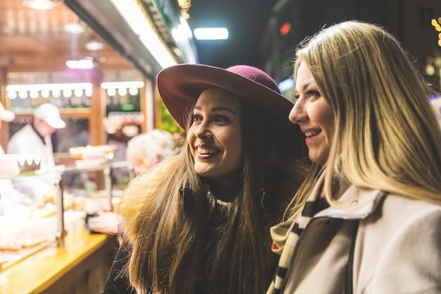 Dos mujeres jóvenes compran comida en el mercado de navidad en munich