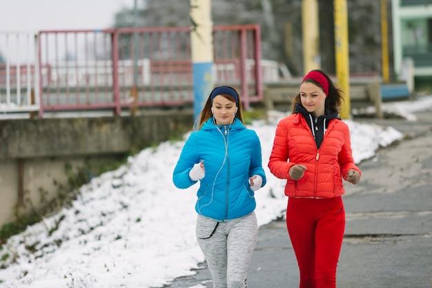 Dos mujeres jóvenes corriendo en la calle en invierno