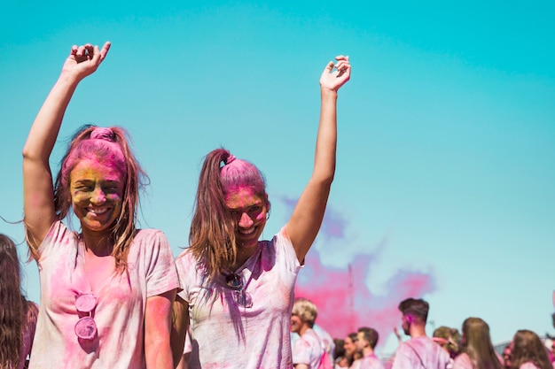 Dos mujeres jóvenes cubiertas con holi bailando en el festival holi.