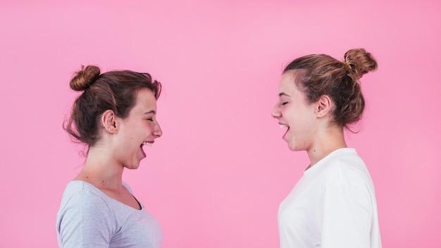 Dos mujeres jóvenes de pie cara a cara gritando contra el fondo rosa