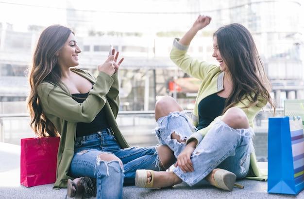 Dos mujeres jóvenes divirtiéndose en el centro de la ciudad.