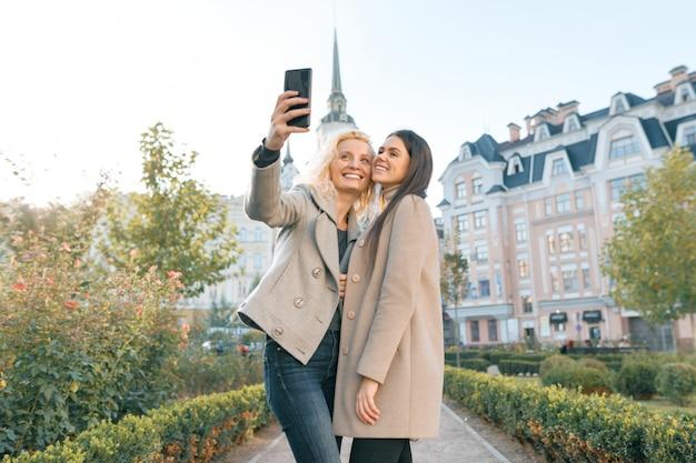 Dos mujeres jóvenes divirtiéndose, mirando el teléfono inteligente