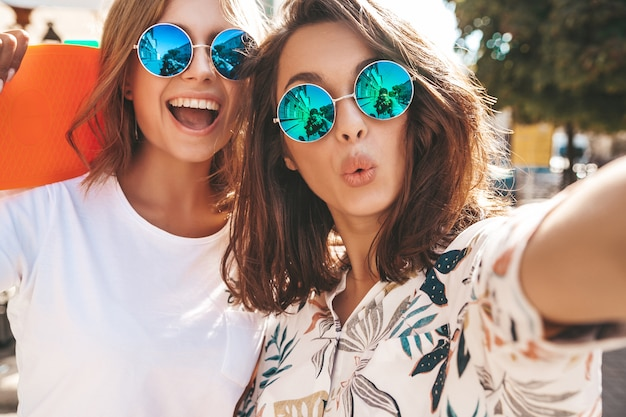 Dos mujeres jóvenes con estilo hippie morena y rubia mujeres en ropa hipster de verano tomando selfie