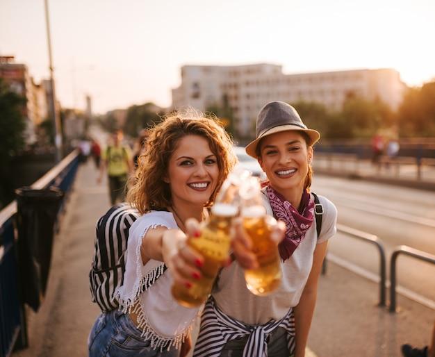 Dos mujeres jóvenes felices con bebidas tintinear botellas en la puesta de sol.