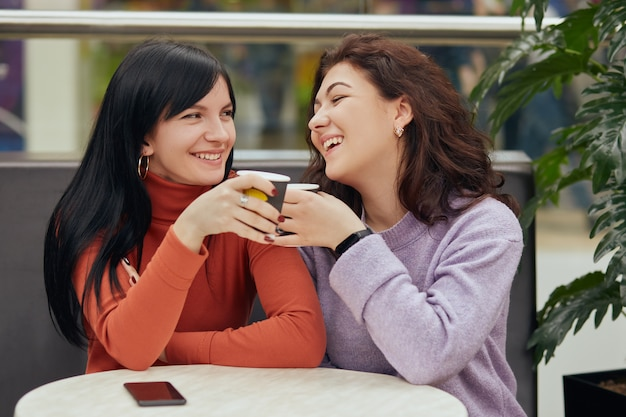 Dos mujeres jóvenes felices bebiendo café en la cafetería y riéndose, vistiendo suéteres casuales, contando historias interesantes, no las han visto desde hace mucho tiempo, disfrutando del tiempo libre.