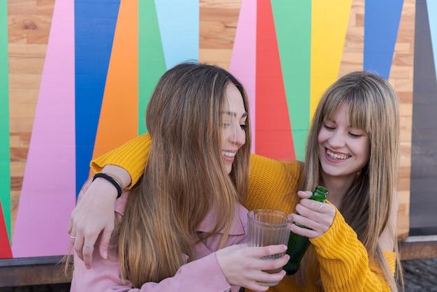 Dos mujeres jóvenes felices brindis con bebida con una pared multicolor