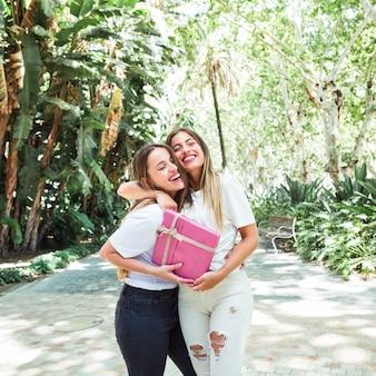 Dos mujeres jóvenes felices con caja de regalo rosa de pie en el parque