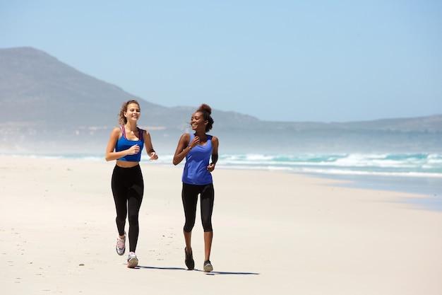 Dos mujeres jóvenes felices corriendo en la playa