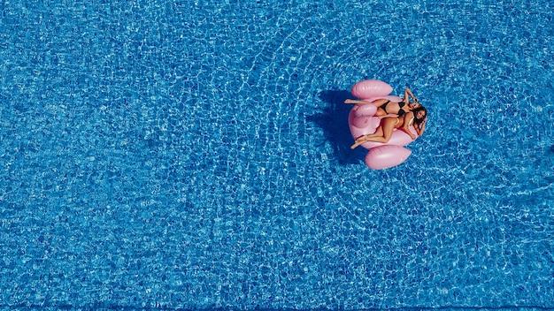 Dos mujeres jóvenes felices con figuras nadan en la piscina de flamencos. vista superior.
