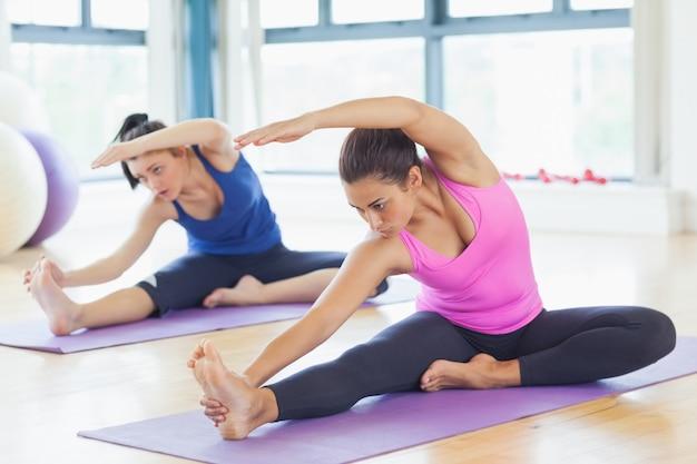 Dos mujeres jóvenes en forma haciendo ejercicios de estiramiento pilato en gimnasio