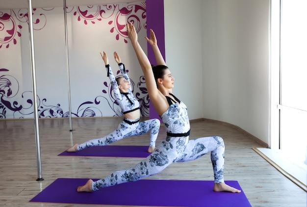 Dos mujeres jóvenes haciendo asanas de yoga