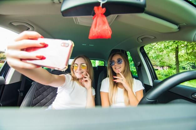 Dos mujeres jóvenes se juntan en un viaje en automóvil conduciendo el automóvil y tomando selfie