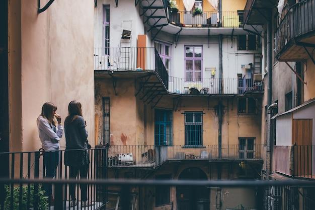 Dos mujeres jóvenes se paran juntas en el patio y lo miran. ventanas coloridas en ciudad vieja o pueblo. viajar juntos