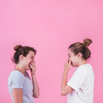 Dos mujeres jóvenes de pie cara a cara riendo con la boca tapada sobre fondo rosa