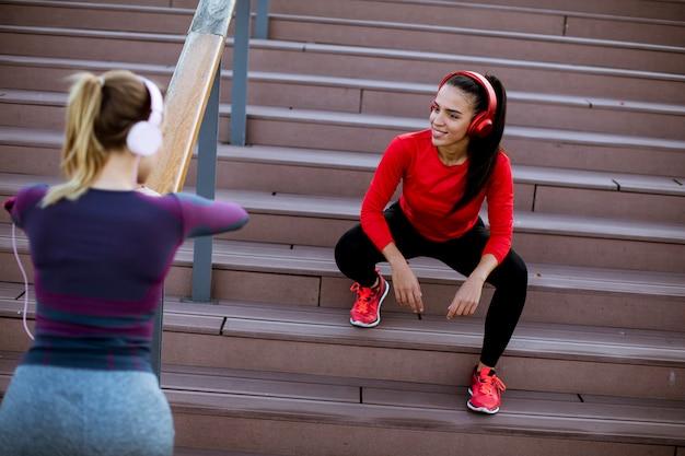 Dos mujeres jóvenes practican estiramientos al aire libre