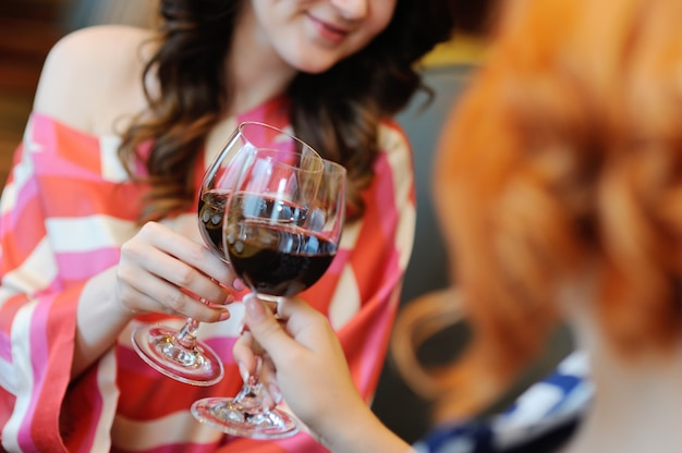 Dos mujeres jovenes que beben el vino en un restaurante. cata de vinos