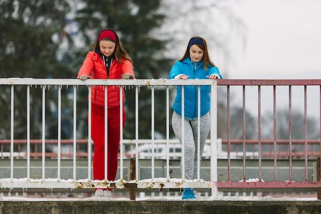 Dos mujeres jóvenes que se extiende cerca de la barandilla