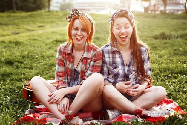Dos mujeres jóvenes riendo hipster riendo