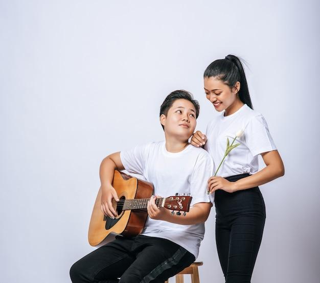 Dos mujeres jóvenes se sentaron en una silla y tocaron la guitarra.
