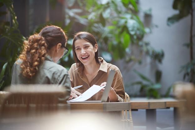 Dos mujeres jóvenes sonrientes discutiendo proyecto empresarial en café