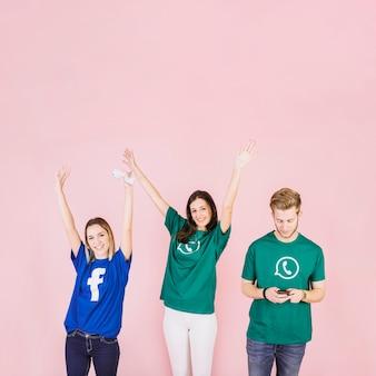 Dos mujeres jóvenes sonrientes levantando sus brazos además de hombre usando teléfono móvil