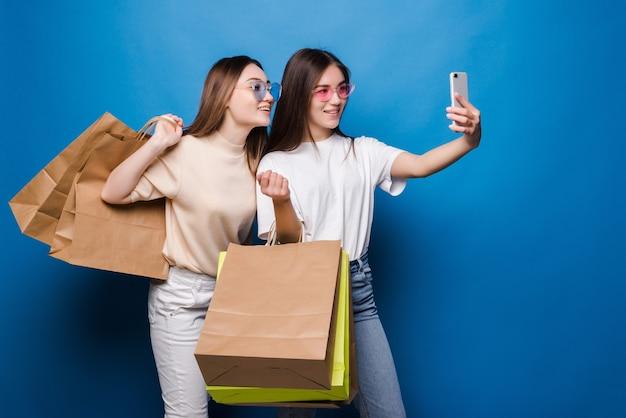 Dos mujeres jóvenes toman selfie en el teléfono con bolsas de papel de colores aislados en la pared azul. concepto de venta en tienda.