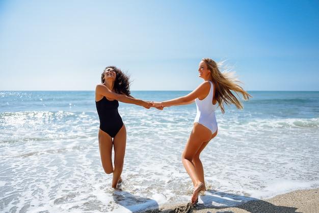 Dos mujeres jóvenes en trajes de baño se divierten con sus manos atrapadas en la playa.