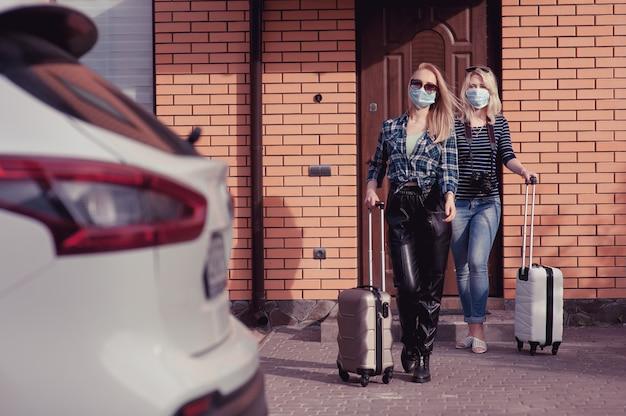 Dos mujeres jóvenes van a viajar en auto