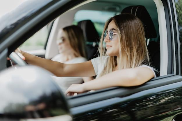 Dos mujeres jóvenes en viaje en coche conduciendo el coche y burlándose. emociones positivas.