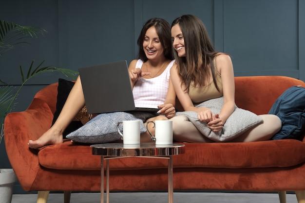 Dos mujeres jóvenes viendo algo divertido en la computadora portátil y riendo mientras están sentados en el sofá