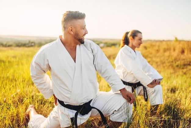 Dos mujeres de karate con instructor masculino en formación