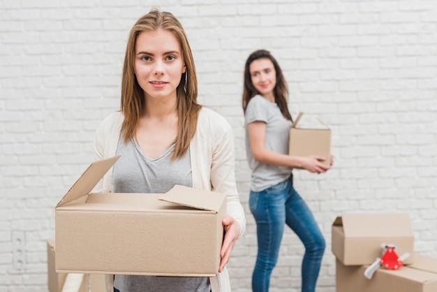 Dos mujeres lesbianas con cajas de cartón en la mano de pie cerca de la pared de ladrillo blanco