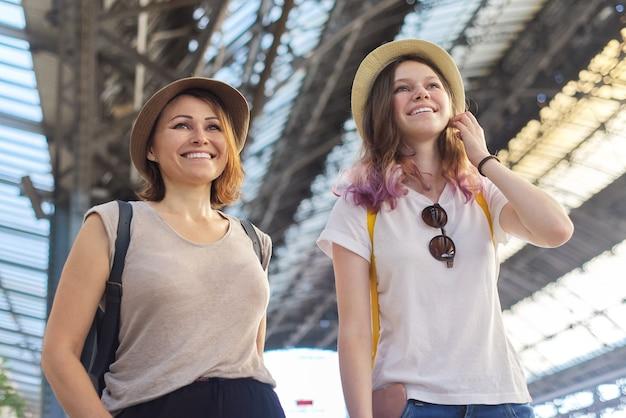 Dos mujeres, madre e hija adolescente caminando con equipaje en la estación de tren