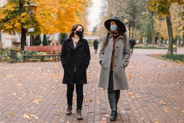 Dos mujeres con máscaras protectoras caminan en el parque
