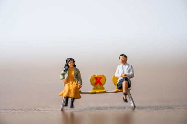 Dos mujeres en miniatura que usan una máscara facial y se sientan en una silla a cierta distancia del público para evitar el brote del virus de la corona covid-19 propagan la infección pandémica. concepto de distanciamiento social.