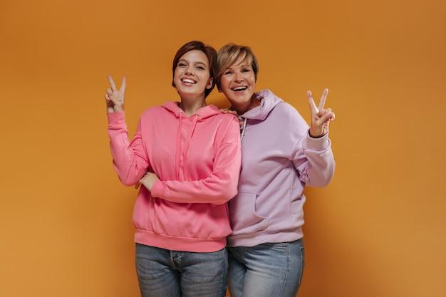 Dos mujeres de moda con peinado corto en una sudadera con capucha ancha de color rosa brillante y jeans geniales sonriendo mostrando el signo de la paz sobre fondo naranja.