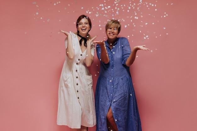 Dos mujeres de moda con peinado corto en vestidos frescos midi sonriendo y posando con confeti sobre fondo aislado.