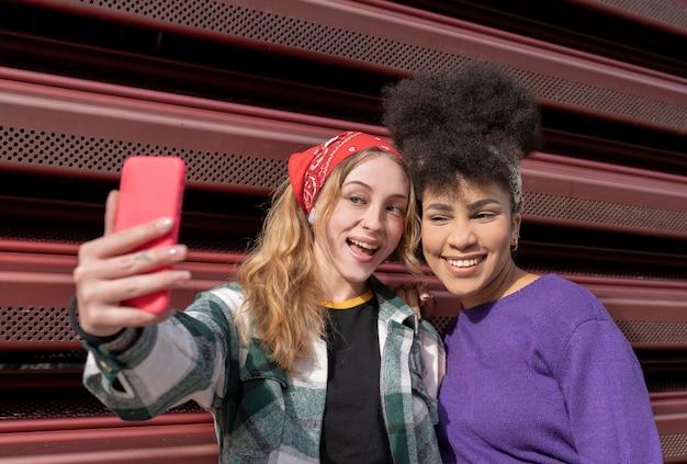 Dos mujeres multirraciales tomando selfie en la calle