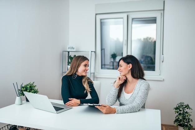 Dos mujeres de negocios casuales que hablan en oficina moderna.