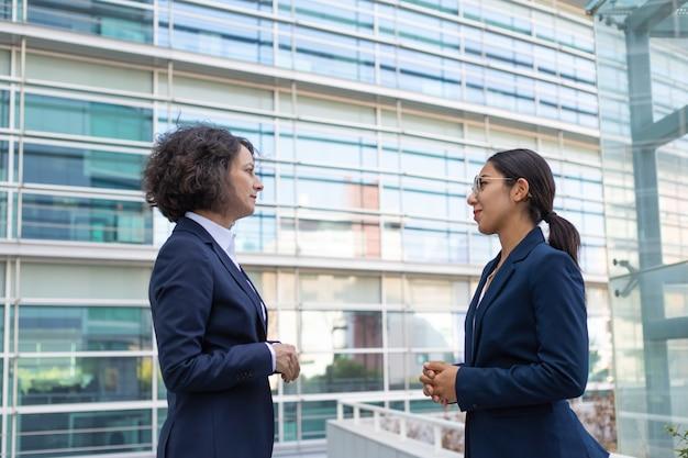 Dos mujeres de negocios discutiendo proyecto cerca de la oficina